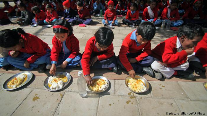 Indian children eat a free mid-day meal at a government school on the outskirts of Jammu, India, Thursday, Feb. 28, 2013. Finance Minister Palaniappan Chidambaram has unveiled a national budget with a promise to put Asia's third largest economy back on a path of high growth and to trim the fiscal deficit. With the country headed for general elections in 2014, government spending on costly social programs was projected to go up substantially. The budget has assigned 100 billion rupees for an ambitious food security program, which will provide subsidized food to the poor. (AP Photo/Channi Anand)