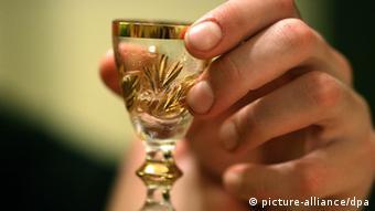 Eine Männerhand hält ein gefülltes kleines Wodkaglas fest