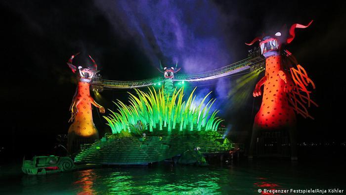 Vier angestrahlte Drachen und Ungeheuer-Figuren auf einem See.