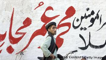 A pro-Taliban supporter standing in front of a graffiti reading 'Ameer-ul-Momneen Mullah Muhammad Omar Mujahid Zindabad (long live holy fighter)' in Killi Nalai, a village near the Pakistan-Afghanistan border (Photo: BANARAS KHAN/AFP/Getty Images)