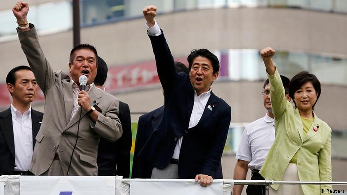 Japan's Prime Minister Shinzo Abe (C), who is also leader of the ruling Liberal Democratic Party, raises his fist with his party members at the start day of campaigning for the July 21 Upper house election in Tokyo July 4, 2013. Abe, riding high in opinion polls on hopes he can revive a stagnant economy, urged voters on Thursday to back his ruling bloc in this month's upper house election and end a six-year policy deadlock. REUTERS/Toru Hanai (JAPAN - Tags: POLITICS ELECTIONS)