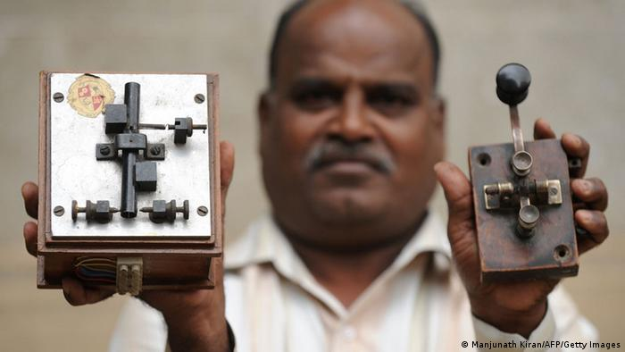 An employee displays an antique telegraph transmitter key (R), which the operator uses to send messages using Morse code, and a telegraph receiver (L) at a telecommunications office in Bangalore on June 13, 2013. (Photo: AFP)