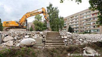 Ein Bagger steht bei Abrissarbeiten an einem DDR-Plattenbau am 24.06.2013 in Leipzig (Sachsen). Leerstand und Abriss waren lange Jahre die prägenden Themen in den ostdeutschen Neubauvierteln. Zehntausende Wohnungen wurden abgerissen. Inzwischen stabilisiert sich die Lage in den Wohngebieten. Im Leipziger Neubauviertel Grünau sind die Bevölkerungszahlen 2012 erstmals seit dem Mauerfall stabil geblieben. Rund 41 000 Menschen wohnen derzeit in Grünau, 1989 waren es 85 000. Foto: Jan Woitas