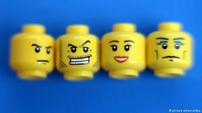 The heads of Lego toy figures on a blue background