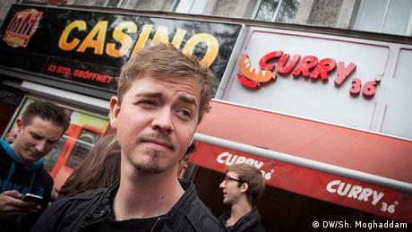 Sänger Kurt steht vor einem Currywurst-Laden. (DW/Sh. Moghaddam)