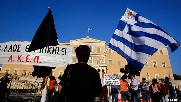 A woman holds a Greek and a black flag as she stands in front of parliament Photo: Yannis Behrakis