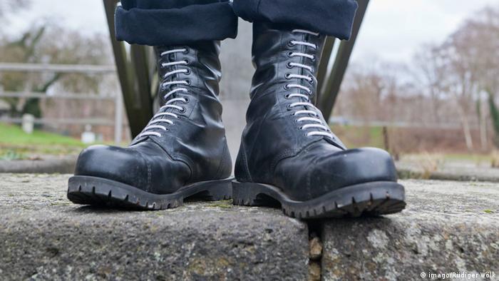 Botas pretas sobre pedra