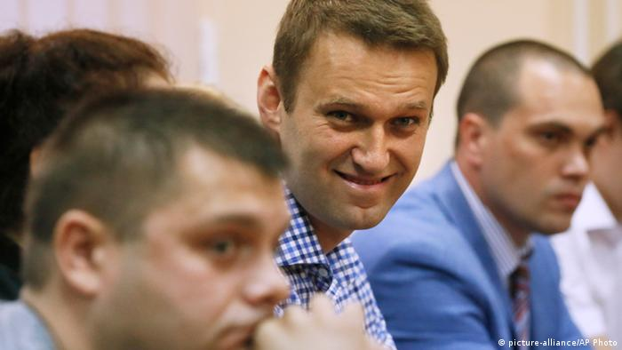 Russian opposition leader Alexei Navalny, center, and his former colleague Pyotr Ofitserov, foreground, listen to judge in a court in Kirov, Russia on Thursday, July 18, 2013. A Russian judge on Thursday found Navalny guilty of embezzlement, a finding that could bring the charismatic anti-corruption blogger and Moscow mayoral candidate up to six years in prison. (AP Photo/Evgeny Feldman)