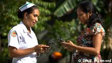 Mana Justa assists a local mum in registering for the Liga Inan program. Mana Justa, the head midwife at Monaco clinic in Same, assists a local pregnant mother in registering her mobile phone with the new mHealth program.