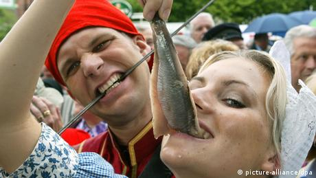 Eine Frau in Trachtenkleidung hält den Matjes mit den Zähnen fest und zieht ihn mit den Fingern am Schwanz hoch. Foto: dpa