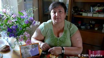 Die Russlanddeutsche Galina Schütz sitzt an einem Tisch. (c) A. Boutsko, DW