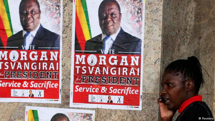 A woman stands beside election posters of Movement For Democratic Change (MDC) leader Morgan Tsvangirai as she speaks on a mobile phone in central Harare July 12 2013. Zimbabwe will hold general elections on July 31. REUTERS/Philimon Bulawayo (ZIMBABWE)