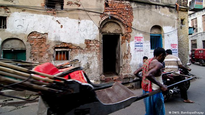 A rickshaw in front of a dilapidated building (Photo: DW/Sirsho Bandopadhayay)