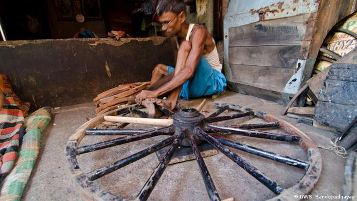 A man fixing a wooden wheel (Photo: DW/Sirsho)