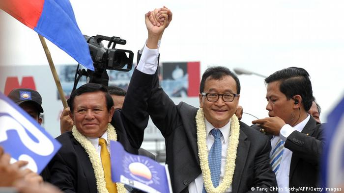 Kem Sokha and Sam Rainsy hold raised hands as the greet supportes on the streets in 2013.