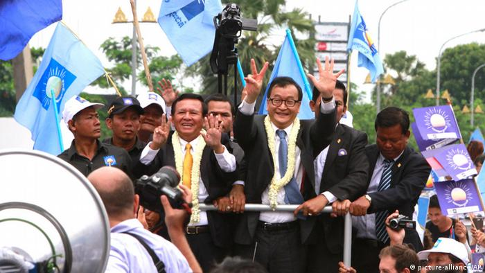 Sam Rainsy, center right, president of Cambodia National Rescue Party (CNRP) greets his supporters together with his party's Vice President Kem Sokha, center left, on his arrival at Phnom Penh International Airport in Phnom Penh, Cambodia, Friday, July 19, 2013. Thousands of cheering supporters greeted Cambodian opposition leader Sam Rainsy as he returned from self-imposed exile Friday to spearhead his party's election campaign against well-entrenched Prime Minister Hun Sen. (AP Photo/Heng Sinith)
