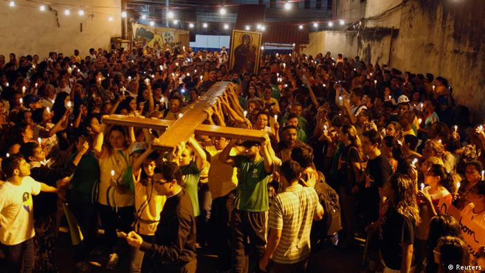 The World Youth Day cross is carried by faithfuls outside a church during a visit to the Rocinha slum in Rio de Janeiro July 18, 2013. Pope Francis will travel to Brazil on his first international trip as pontiff in July. The main purpose of the trip is for the pope to preside at the Catholic Church's World Day of Youth. The Pope's participation in World Youth Day events starts on the evening of July 25 in Rio's famed Copacabana Beach area and culminates with a huge open-air Mass in the Guaratiba area of the city on July 28. REUTERS/Pilar Olivares (BRAZIL - Tags: POLITICS RELIGION)