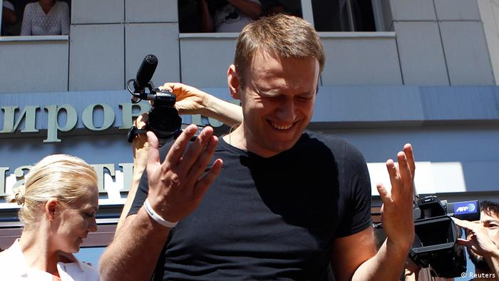 Russian opposition leader Alexei Navalny (R) reacts as he talks to the media, with his wife Yulia (L) standing nearby, outside a court building in Kirov, July 19, 2013. A Russian court temporarily released Navalny from custody on Friday, but placed him under travel restrictions, while he awaits the outcome of an appeal against his sentence to five years in jail. REUTERS/Sergei Karpukhin (RUSSIA - Tags: CRIME LAW POLITICS CIVIL UNREST)