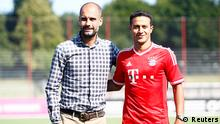 Spain's soccer player Thiago Alcantara (R) and Bayern Munich's head coach Pep Guardiola pose during the official presentation of Bayern Munich's new player at the training area in Munich July 16, 2013. REUTERS/Michaela Rehle (GERMANY - Tags: SPORT SOCCER)