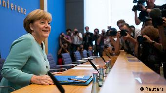 German Chancellor Angela Merkel arrives for a news conference at Bundespressekonferenz in Berlin July 19, 2013. REUTERS/Thomas Peter (GERMANY - Tags: POLITICS)