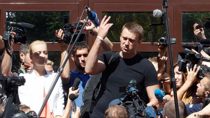 Russian opposition leader Alexei Navalny (R, centre) talks to the media, with his wife Yulia (L, centre) standing nearby, outside a court building in Kirov, July 19, 2013. A Russian court temporarily released Navalny from custody on Friday, but placed him under travel restrictions, while he awaits the outcome of an appeal against his sentence to five years in jail. REUTERS/Sergei Karpukhin (RUSSIA - Tags: CRIME LAW POLITICS CIVIL UNREST)