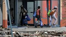Authorities said looting was becoming a problem at a number of stores and casinos along the Mississippi Gulf Coast Tuesday, Aug. 30, 2005 in Biloxi, Miss. These individuals were photographed exiting a closed store along the beachfront carrying bags of merchandise. (AP Photo/Rogelio Solis)