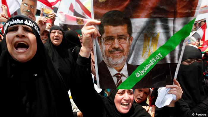 A supporter of deposed Egyptian President Mohamed Mursi holds up a sign with an image of Mursi as they protest at the Rabaa Adawiya square where they are camping at in Cairo July 19, 2013. Thousands of supporters of Mursi rallied in Cairo on Friday to demand the restoration of the ousted Islamist leader, with his opponents also planning protests nearby. REUTERS/Mohamed Abd El Ghany (EGYPT - Tags: POLITICS CIVIL UNREST RELIGION)