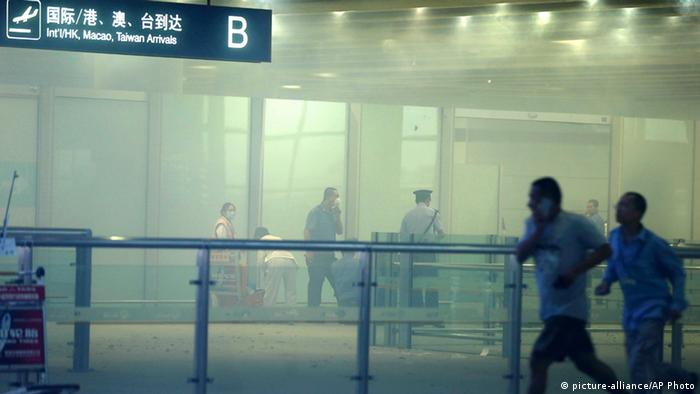 In this photo released by China's Xinhua News Agency, medical workers and policemen work at the terminal 3 of the Beijing International Airport in Beijing, Saturday, July 20, 2013. Chinese state media said that a man set off a homemade bomb in Terminal 3 of the Beijing International Airport, but that no one besides the man was injured and order has been restored. (AP Photo/Xinhua, Chen Jianli) NO SALES