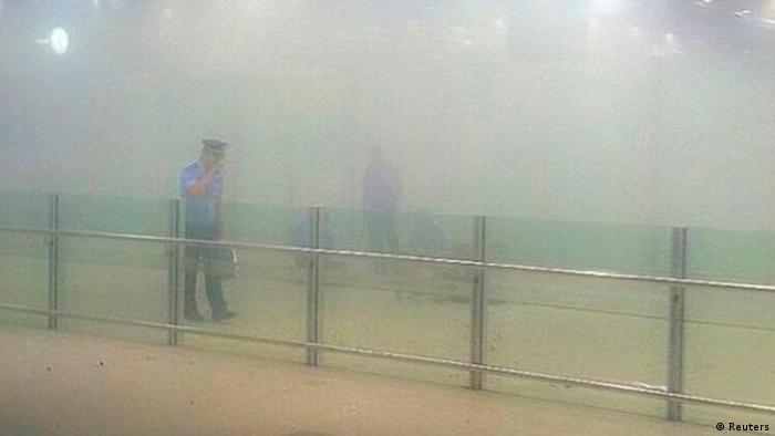 A policeman stands amid smoke at the arrival gate B after an explosion at the Terminal 3 of Beijing Capital International Airport in Beijing, July 20, 2013. A man in a wheelchair detonated a home-made explosive in Beijing airport on Saturday evening, injuring himself and sending smoke billowing through the exit area of the international arrivals section of Terminal 3. REUTERS/Stringer (CHINA - Tags: DISASTER CIVIL UNREST TRANSPORT) CHINA OUT. NO COMMERCIAL OR EDITORIAL SALES IN CHINA
