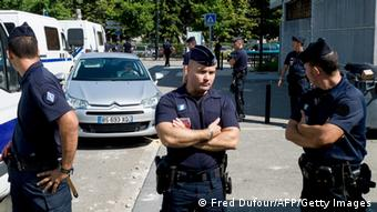 Policemen stand next to a police station in Trappes