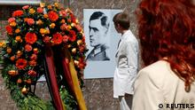 Visitors walk past a portrait of Claus Schenk Graf von Stauffenberg, who conspired to overthrow Adolf Hitler, in the Bendlerblock building during a ceremony in Berlin July 20, 2013. Germany on Saturday remembered a group of military officers led by Stauffenberg who conspired to assassinate Adolf Hitler on July 20, 1944 and overthrow the Nazi regime. REUTERS/Tobias Schwarz (GERMANY - Tags: POLITICS MILITARY ANNIVERSARY)
