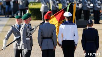 Five soldiers, one is Holding a German flag (Photo: REUTERS/Tobias Schwarz)