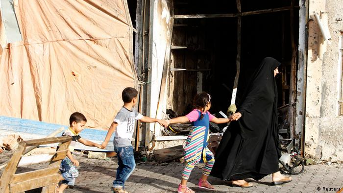 A family walks past the site of a car bomb attack at the neighbourhood of Tobchi in Baghdad, July 21, 2013. Multiple car bombings in predominantly Shi'ite districts of Baghdad killed at least 30 people on Saturday, police and medics said, the latest in a series of attacks that threaten to sink Iraq once again into full-blown sectarian conflict. REUTERS/Thaier al-Sudani (IRAQ - Tags: CIVIL UNREST POLITICS)