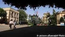 Egyptian men pass by the Shura Council, in Cairo, Egypt, Saturday, June 1, 2013. When voters went to the polls more than a year ago to vote for Egypt's upper house of parliament, most presumed the legislature would be the powerless talk shop that it had been for 30 years. Few candidates were known outside their families, parties or neighborhoods. Only seven percent of the electorate bothered to cast a ballot. Thanks to the twists and turns of the rocky transition that followed Egypt's 2011 uprising, the Shura Council finds itself the sole law-making body in the land. This accidental legislature is now back in the spotlight ahead of an expected court ruling on its disputed legal status _ a move that could see it dissolved. (AP Photo/Hassan Ammar)