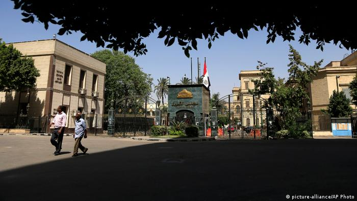 Egyptian men pass by the Shura Council, in Cairo, Egypt, Saturday, June 1, 2013. . (AP Photo/Hassan Ammar)