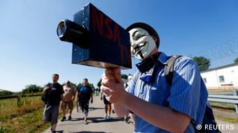 A protester wearing a Guy Fawkes mask holds a paper-made mock TV camera during a demonstration against the National Security Agency (NSA) and in support of U.S. whistleblower Edward Snowden, outside the Dagger Complex, which is used by the U.S. Army intelligence services, in Griesheim, 20 km (12.4 miles) south of Frankfurt, July 20, 2013. REUTERS/ Kai Pfaffenbach (GERMANY - Tags: POLITICS CIVIL UNREST CRIME LAW TPX IMAGES OF THE DAY)