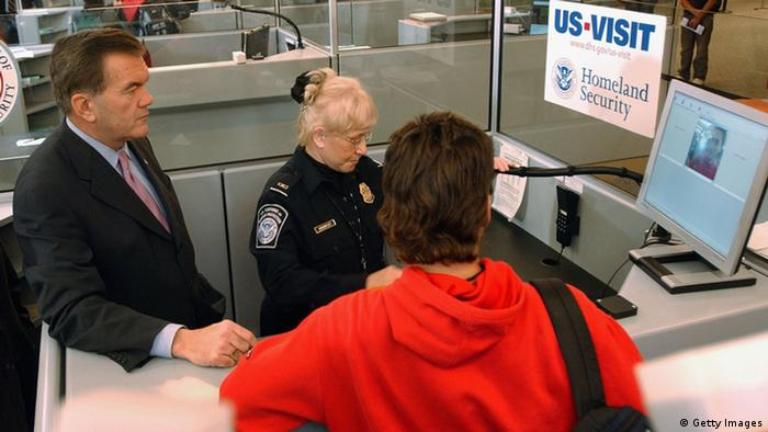 ATLANTA, GA - JANUARY 5: Homeland Security Secretary Tom Ridge, left, watches Customs and Border Protection officer Mary Armbrust use the new US-VISIT biometric program at Hartsfield-Jackson International Airport in Atlanta, Georgia, January 5, 2004. The system fingerprints and photographs visitors to the United States who require visas. (Photo by Erik S. Lesser/Getty Images)