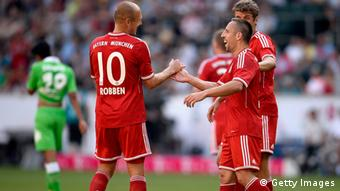 MOENCHENGLADBACH, GERMANY - JULY 21: Franck Ribery of FC Bayern Muenchen celebrates with teammate Arjen Robben after scoring his team's second goal during the Telekom 2013 Cup final between FC Bayern Muenchen and Borussia Moenchengladbach on July 21, 2013 in Moenchengladbach, Germany. (Photo by Dennis Grombkowski/Bongarts/Getty Images)