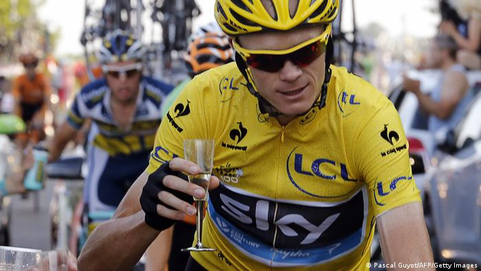 Overall leader's yellow jersey Britain's Christopher Froome holds a glass of Champagne as he rides next to his team car, during the 133.5 km twenty-first and last stage of the 100th edition of the Tour de France cycling race on July 21, 2013 between Versailles and Paris. (Photo via PASCAL GUYOT/AFP/Getty Images)