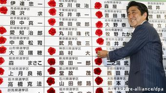 ©Kyodo/MAXPPP - 22/07/2013 ; TOKYO, Japan - Japanese Prime Minister and Liberal Democratic Party President Shinzo Abe puts flowers on the name of winning party candidates in the House of Councillors election at the LDP's headquarters in Tokyo on July 21, 2013. (Kyodo)
