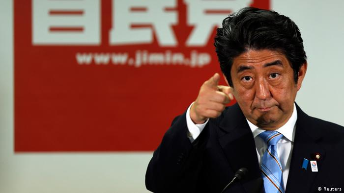 Japan's Prime Minister and the leader of the ruling Liberal Democratic Party (LDP), Shinzo Abe, points to a reporter during a news conference following a victory in the upper house elections by his ruling coalition, at the LDP headquarters in Tokyo July 22, 2013. Abe said on Monday that his government would lose public confidence if it retreated from reform. REUTERS/Issei Kato (JAPAN - Tags: POLITICS ELECTIONS TPX IMAGES OF THE DAY)