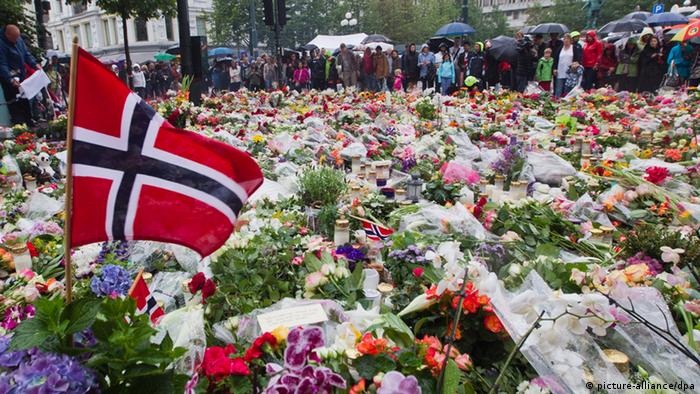 photo shows Norwegian flags, flowers and candles commemorating the victims of the attacks placed in front of the Domkirke church in central Oslo, Norway.