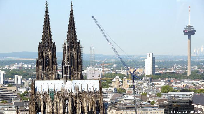 Ein Kran hebt am 22.07.2013 in Köln ein Baugerüst vom Dom ab. Foto: Federico Gambarini/dpa