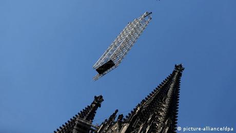 Ein Kran hebt am 22.07.2013 in Köln (Nordrhein-Westfalen) ein Baugerüst vom Dom ab. Bei dem größten Kran-Einsatz in der Geschichte des Kölner Doms, ist in über 100 Meter Höhe ein Baugerüst abgenommen worden. Das Gerüst wurde vor mehr als zehn Jahren für Sanierungsarbeiten an einem der markanten Türme zusammengebaut. Foto: Federico Gambarini/dpa