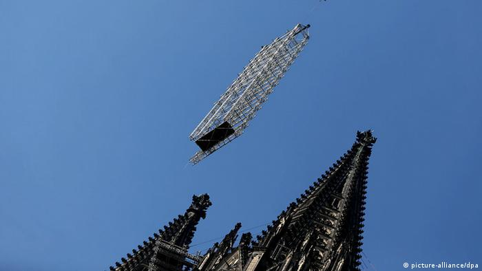 A crane moves scaffolding (photo: Federico Gambarini/dpa)