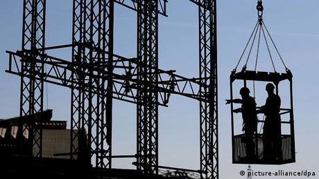Arbeiter sichern am 22.07.2013 in Köln (Nordrhein-Westfalen) am Dom ein Baugerüst, das an einem Kran hängt. Bei dem größten Kran-Einsatz in der Geschichte des Kölner Doms, ist in über 100 Meter Höhe ein Baugerüst abgenommen worden. Das Gerüst wurde vor mehr als zehn Jahren für Sanierungsarbeiten an einem der markanten Türme zusammengebaut. Foto: Oliver Berg/dpa +++(c) dpa - Bildfunk+++