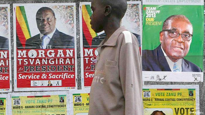 Man walking in front of election signs for Mugabe and Tsvangirai