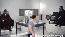 Ein Ausstellungsbesucher geht am 18.07.2013 in Düsseldorf (Nordrhein-Westfalen) an einem Bild von der Aktion Leben mit Pop. Eine Reproduktion des Kapitalistischen Realismus im Möbelhaus Berges mit Konrad Lueg (l) und Gerhard Richter (r) aus dem Jahr 1963 vorbei. Die Kunsthalle Düsseldorf zeigt in ihrer Ausstellung Leben mit Pop. Eine Reproduktion des Kapitalistischen Realismus Reproduktionen von Kunstwerken von Gerhard Richter, Konrad Lueg, Sigmar Polke und Manfred Kuttner. Foto: Federico Gambarini/dpa +++(c) dpa - Bildfunk+++ pixel