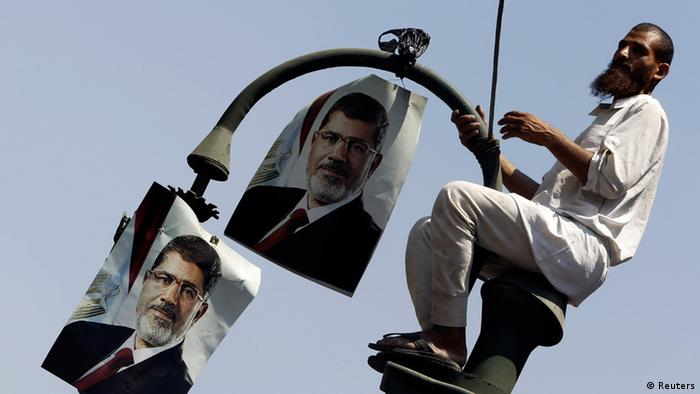 member of the Muslim Brotherhood and supporter of ousted Egyptian President Mohamed Mursi places posters of Mursi on a lamp post during a protest in front of the courthouse and the Attorney General's office in Cairo July 22, 2013. The family of ousted Egyptian President Mohamed Mursi said on Monday it would take legal action against the army, accusing it of abducting the country's first democratically-elected president. REUTERS/Amr Abdallah Dalsh (EGYPT - Tags: POLITICS CIVIL UNREST RELIGION)