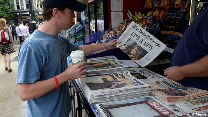 A man buys a newspaper displaying the news of the Royal birth by Britain's Catherine, Duchess of Cambridge in central London, July 23, 2013. Already touted as one of the most famous babies in the world, the first child of Prince William and wife Kate faces a life in the spotlight like no previous royal, severely testing the couple's desire to give their offspring a normal life. REUTERS/Paul Hackett (BRITAIN - Tags: ROYALS ENTERTAINMENT MEDIA HEALTH)